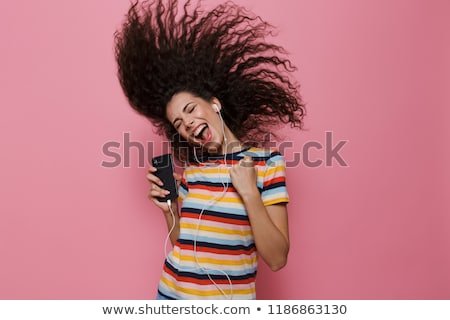 Beautiful woman posing isolated over pink background listening music by earphones dancing. Stock photo © deandrobot