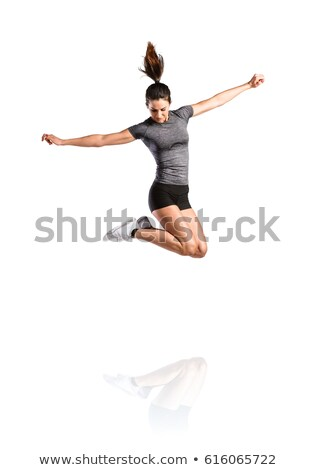 Stock photo: Beautiful strong young sports woman jumping isolated indoors.