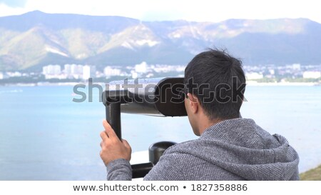 a man looks in coin operated binoculars at the sea stock photo © galitskaya