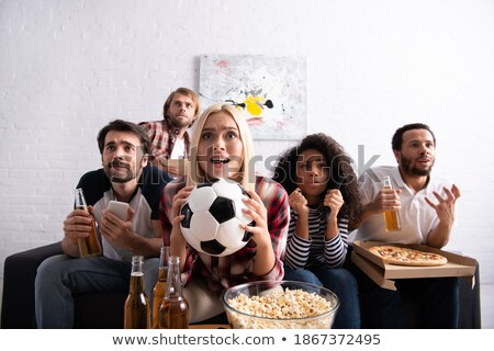 Tense young sports fans with snack and beer watching football broadcast Stock photo © pressmaster