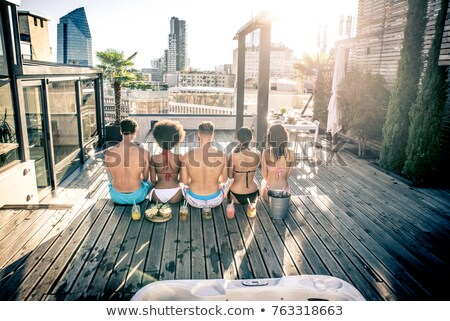 happy friends with drinks hugging at rooftop party Stock photo © dolgachov