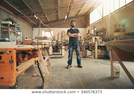 Stock photo: Happy carpenter in his wood workshop