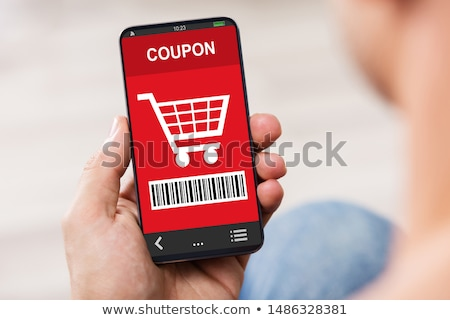 Man's Hand Holding Mobile Phone With Shopping Coupon Stock photo © AndreyPopov