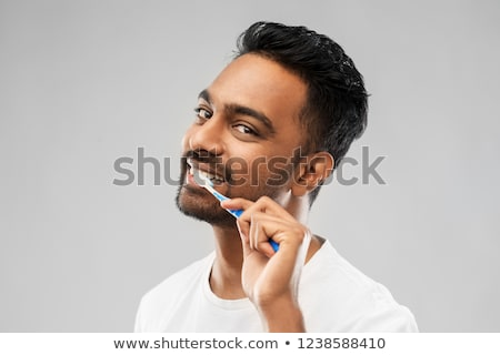 indian man with toothbrush over gray background Stock photo © dolgachov