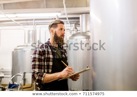men with clipboard at brewery kettle or beer plant stock photo © dolgachov