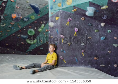 Restful schoolboy in activewear sitting against climbing wall after training Stock photo © pressmaster
