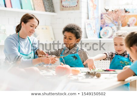 Pretty young teacher showing cute African schoolboy halloween decorations Stock photo © pressmaster