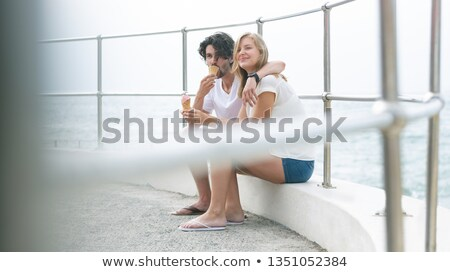 Side view of young Caucasian couple siting at promenade while having ice cream cone on a sunny day Stock photo © wavebreak_media