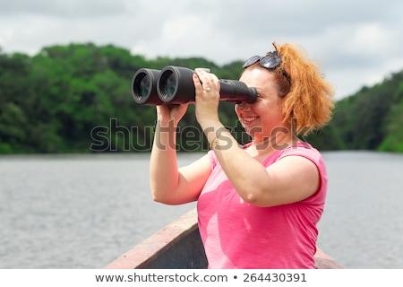 Woman on a boat with binocular watching birds Stock photo © Kzenon