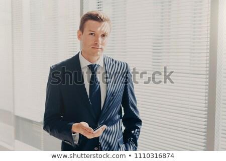 Prosperous male director sends message and multimedia files via smart phone, synchronizes phone data Stock photo © vkstudio