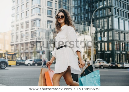portrait of young woman with shopping bags smiling and walking stock photo © hasloo