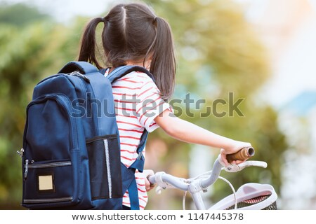 Cheerful little girl goes on a bicycle stock photo © pzaxe