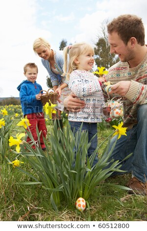 Mother And Children In Daffodil Field With Decorated Easter Eggs Stock photo © monkey_business
