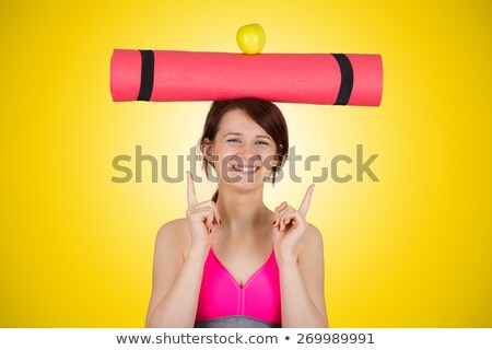 Young woman carrying exercise mat smiling and pointing up stock photo © bmonteny