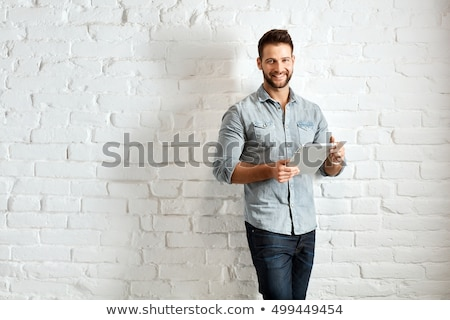 young casual man leaning on a brick wall stock photo © feedough