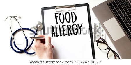 hand with pen writing the word allergy stock photo © zerbor