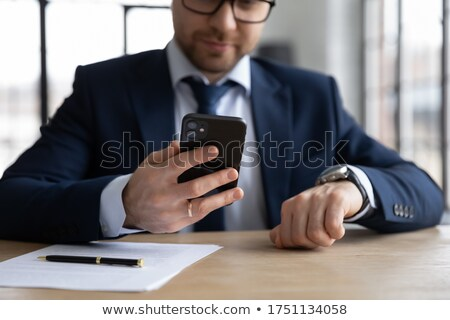 Businessman checking time on watch at office desk Stock photo © stevanovicigor