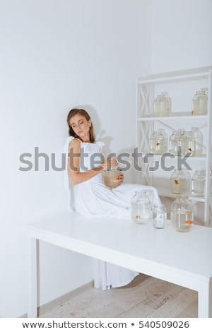 Stock photo: Relaxed young woman with gold fishes in jars