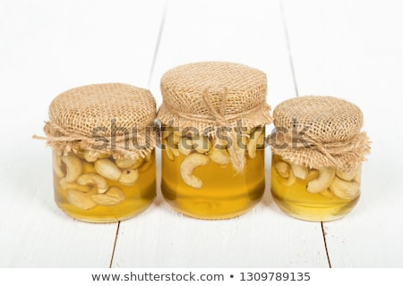 Honey in a glass jar covered with burlap stock photo © Cipariss