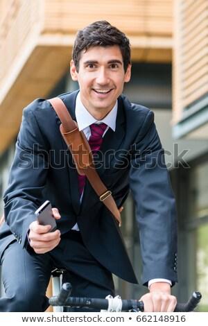 Multitasking young businessman riding a bicycle to work Stock photo © Kzenon