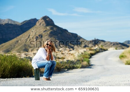 Woman sitting on petrol can in the road Stock photo © IS2