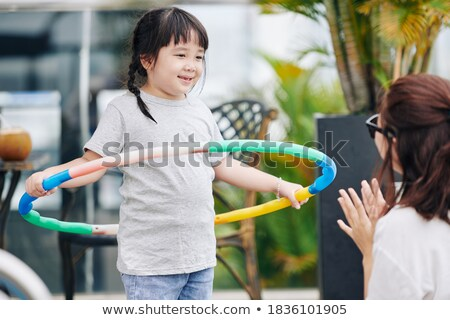 Woman playing with hula hoop in pool Stock photo © IS2
