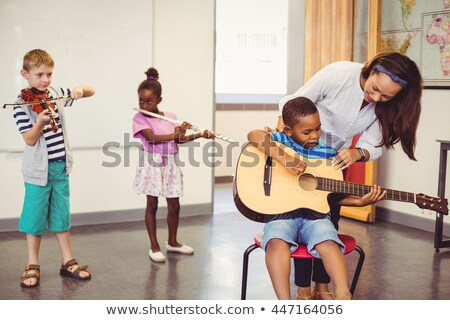 Stock foto: Chulmädchen · und · Lehrer, · die · Gitarre · im · Musikunterricht · spielen
