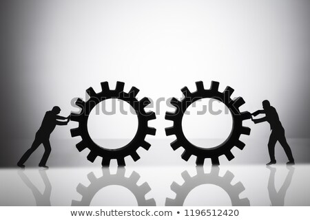 Silhouette Of Two Businesspeople Joining Gears Stock photo © AndreyPopov
