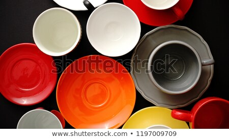 Colorful empty plates and saucers over black background. Stock photo © dash