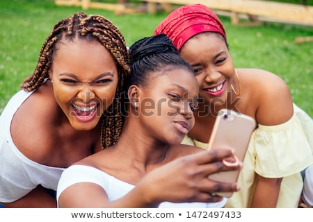 photo of cute african american woman smiling and holding mobile stock photo © deandrobot