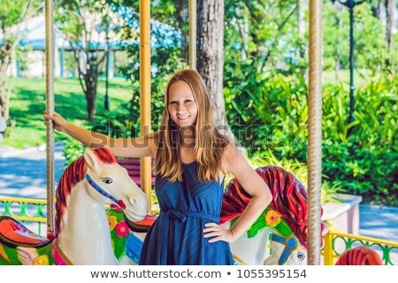 Woman enjoying in funfair and riding on colorful carousel house stock photo © galitskaya