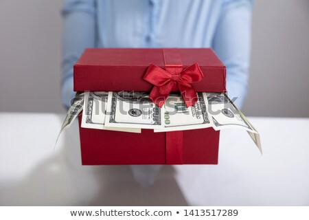 hand holding gift box filled with currency stock photo © andreypopov