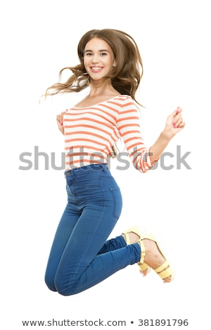 Full length portrait of young brunette girl jumping and holding her hair in hands. Smiling and emoti stock photo © studiolucky