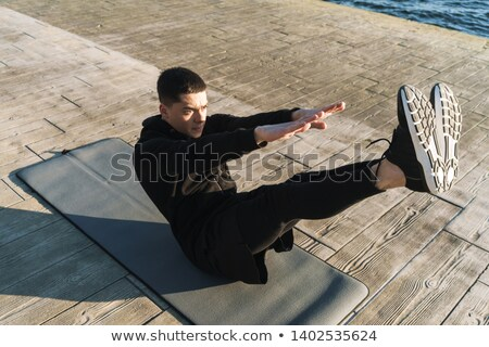 Photo of young sportsman 20s in tracksuit lying on mat, and doin Stock photo © deandrobot