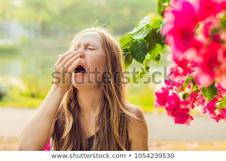 Pollen allergy concept. Young woman is going to sneeze. Flowering trees in background ストックフォト © galitskaya