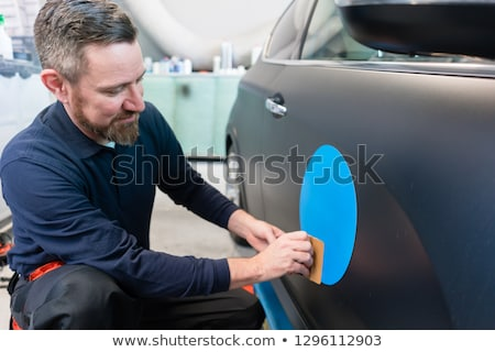 Man putting sticker with company slogan on a car Stock photo © Kzenon