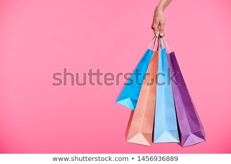 Four colorful paperbags held by hand of female shopaholic Stock photo © pressmaster