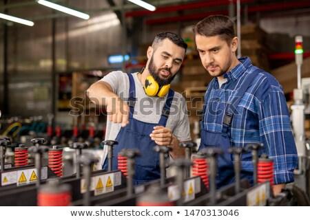 Młodych stażysta patrząc przemysłowych wyposażenie słuchania Zdjęcia stock © pressmaster