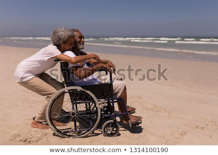 Side view of woman embracing disabled senior man on beach in the sunshine Stock photo © wavebreak_media