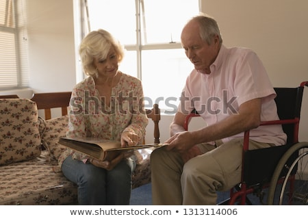 Front view of senior couple looking at photo album in living room. The senior woman are sitting on s Stock photo © wavebreak_media
