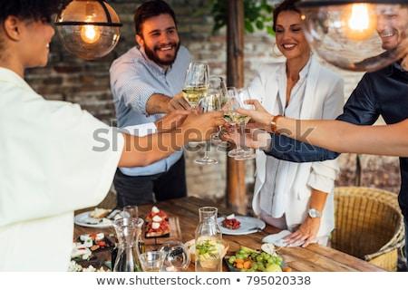 People cheering with white wine and rising glasses on celebratio Stock photo © dashapetrenko