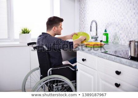 Handicapped Man Sitting On Wheelchair In Kitchen Stock photo © AndreyPopov