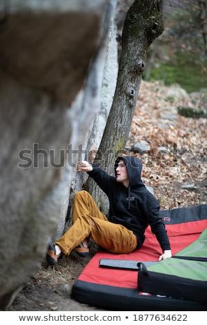 A rock climber climbing on a boulder rock outdoors. Group of fri Stock photo © lightpoet