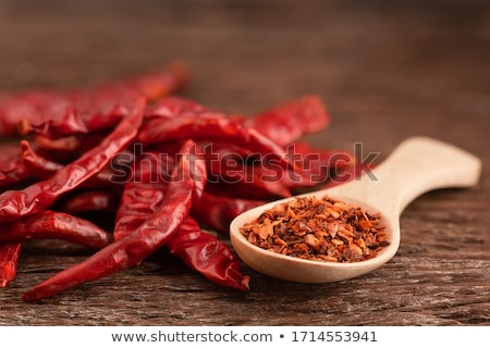 Flakes of red hot chili pepper in wooden spoon closeup on a kitc Stock photo © cookelma