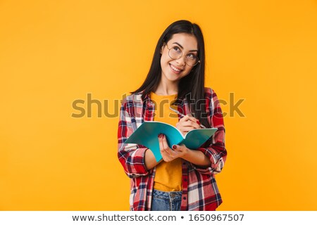Photo of thinking brunette woman smiling while making notes in diary Stock photo © deandrobot