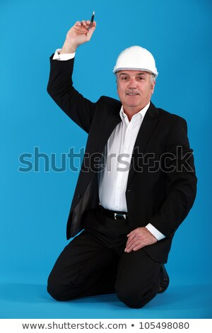 Mature architect kneeling on the floor with arm raised Stock photo © photography33