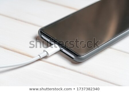 white smart phone charging with usb cable on black table stock photo © maxpro