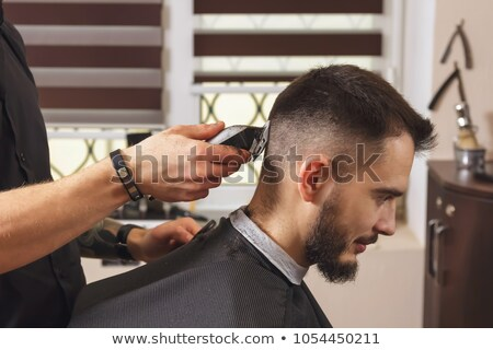 Young hairstylist making men's haircut to a bearded male  Stock photo © deandrobot