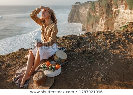 young woman sits on the sand on the edge of the sea stock photo © Paha_L