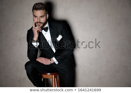 man in tuxedo holding his chin and thinking  Stock photo © feedough